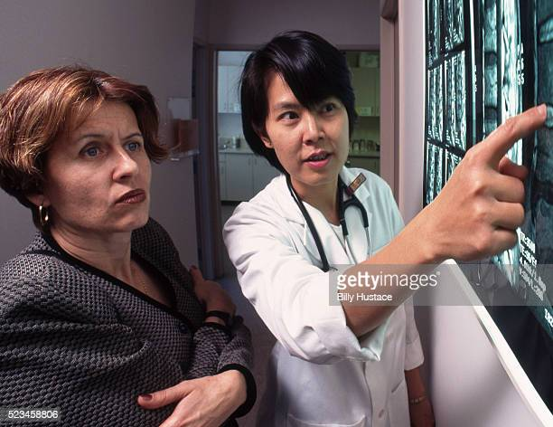 Two professional woman discussing an x-ray in a medical office.