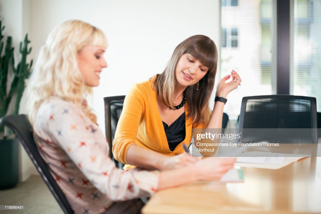 Two professional women working together at a table : Stock Photo