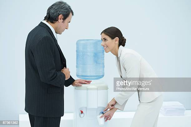 two professionals chatting beside water cooler, woman filling disposable cup - femme entre deux hommes photos et images de collection