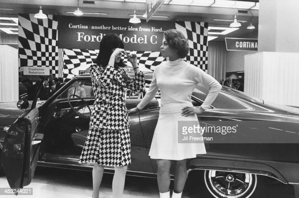 Two promotional models talk on the exhibition stand at a car show New York City 1966