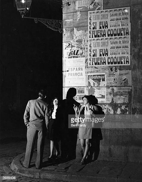 Two prostitutes talking to a client on a Barcelona street corner Original Publication Picture Post 5243 Barcelona a City in Ferment pub 1951