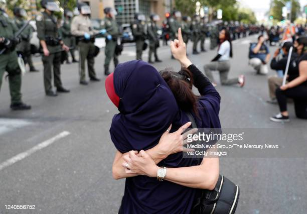 Two protesters embrace during a protest of the killing of George Floyd outside of San Jose City Hall in downtown San Jose Calif on Sunday May 31 2020