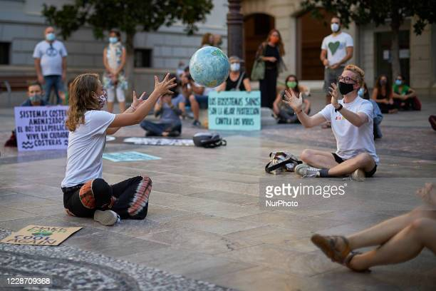 Two protesters play with a ball shaped like a planet earth during a pacific concentration in Plaza del Carmen Square on September 25, 2020 in...