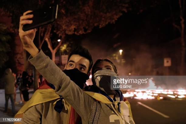Two protesters take a selfie photo as barricades burn in the background during a demonstration called by the local Republic Defence Committees in...