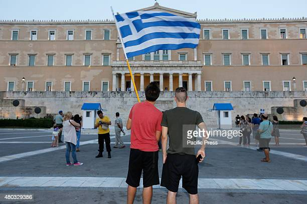 SQUARE ATHENS ATTICA GREECE Two protesters wave a Greek flag at the antiausterity protest Members of the Communist Trade Union PAME rallied outside...