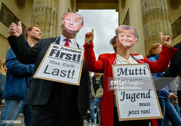 """Two protesters wearing masks of US President Donald Trump and German Chancellor Angela Merkel hold signs reading """"Mr President First, Mrs Earth Last""""..."""