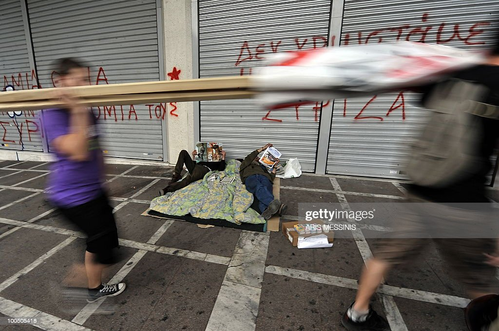 Two protestors carrying a banner walk past two homeless men before a demonstration against government's austerity measures in central Athens on May 12, 2010. Greece was to receive a first dose of 5.5 billion euros from the IMF under a massive bailout loan agreed with the EU in exchange for austerity cuts which are sparking new demonstrations. The EU has agreed to give Greece 14.5 billion euros as a first tranche, raising the instalment total to 20 billion euros. Athens needs to make a payment of nine billion euros on a maturing 10-year bond on May 19.