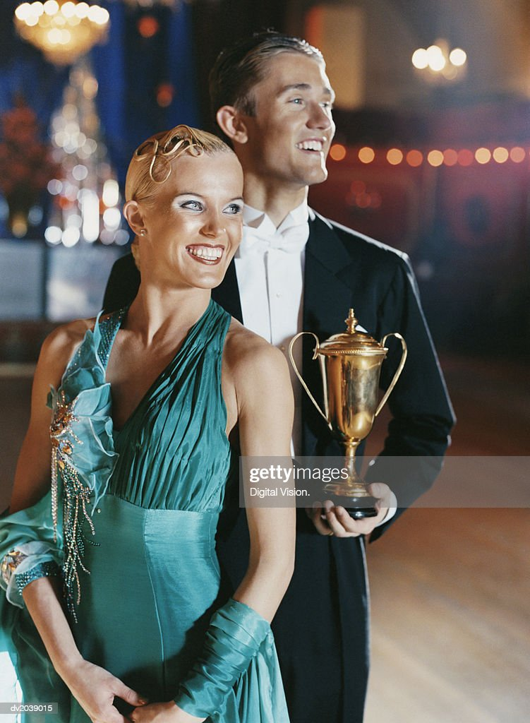 Two Proud Ballroom Dancers Standing Together on a Dance Floor, with the Man Holding a Trophy : Stock Photo
