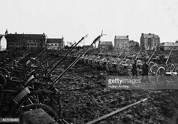 Two Prussian soldiers stand amidst the captured French artillery guns and limbers following the Battle of Sedan during the FrancoPrussian War on 10...