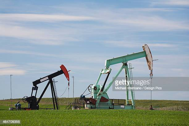 Two Pump Jacks In A Field With Clouds And Blue Sky East Of Airdrie