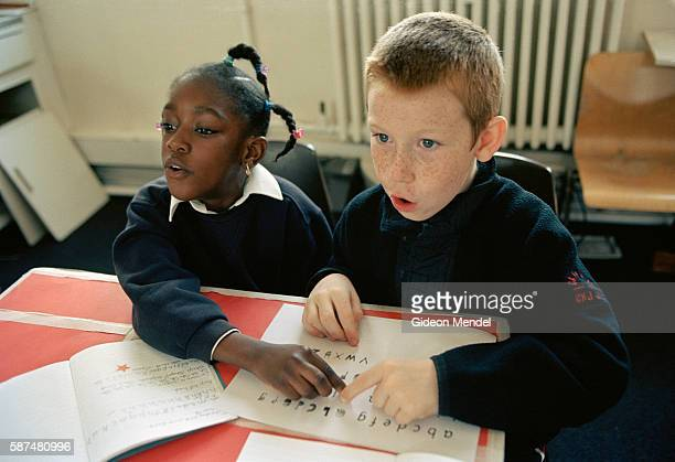 Two pupilsl at Millfields Community School practice the letters of the alphabet during an RML lesson This programme teaches children to read and...