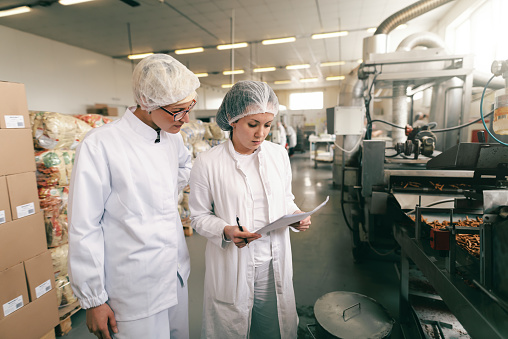 Two quality professionals in white sterile uniforms checking quality of salt sticks while standing in food factory. 1131834506