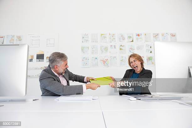 Two quarreling colleagues at their desks in an office