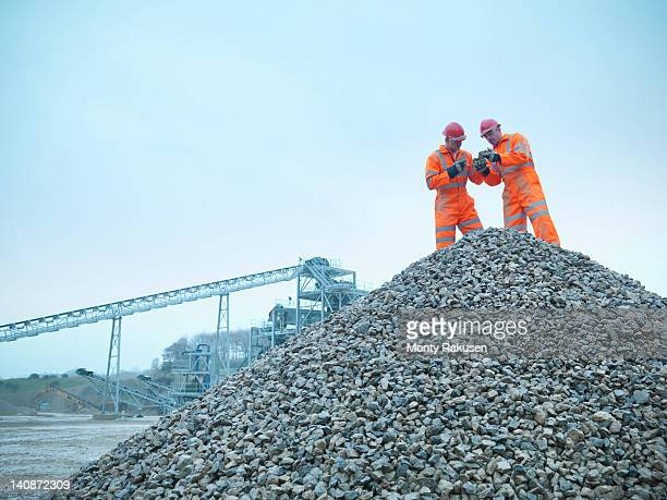 Two quarrymen inspecting stockpiles of quarried stone