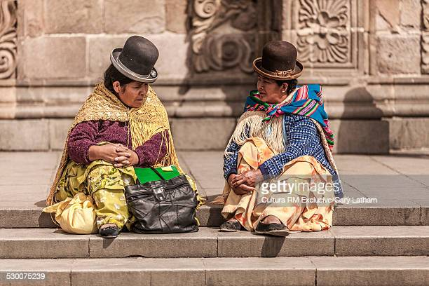 Two quechua women wearing bowler hats sitting on steps, La Paz, Bolivia, South America