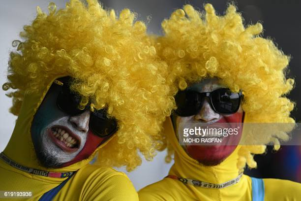Two race fans pose before the start of the Malaysian MotoGP race at the Sepang International circuit on October 30 2016 / AFP / MOHD RASFAN