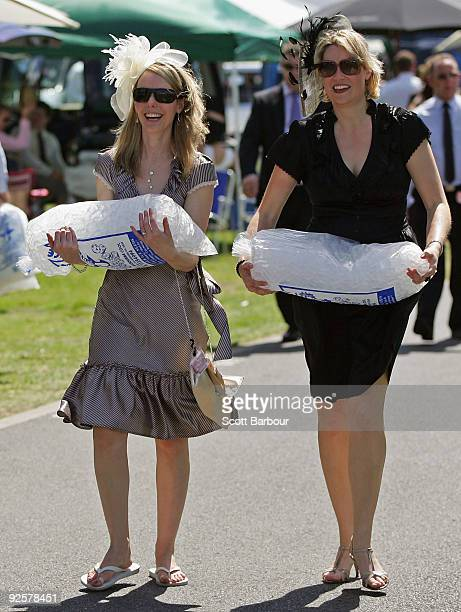 Two Racegoers Carry Bags Of Ice Back To Their Cars Keep Drinks Cool In