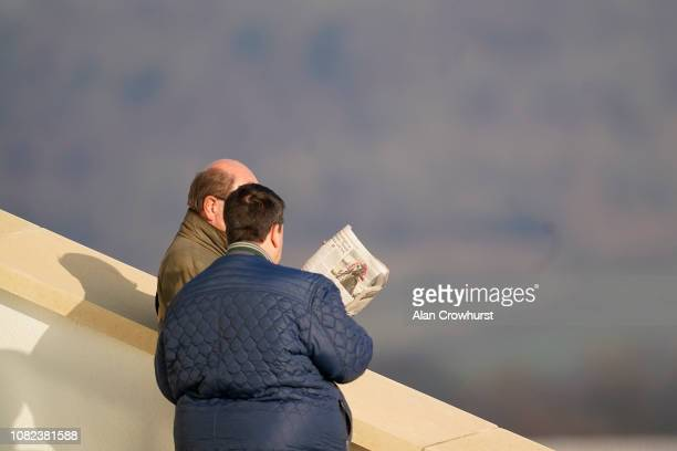 Two racegoers check out the trade paper at Cheltenham Racecourse on December 14 2018 in Cheltenham England