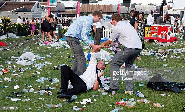Two racegoers help their friend to his feet after he fell over after the AAMI Victoria Derby Day at Flemington Racecourse on October 31 2009 in...