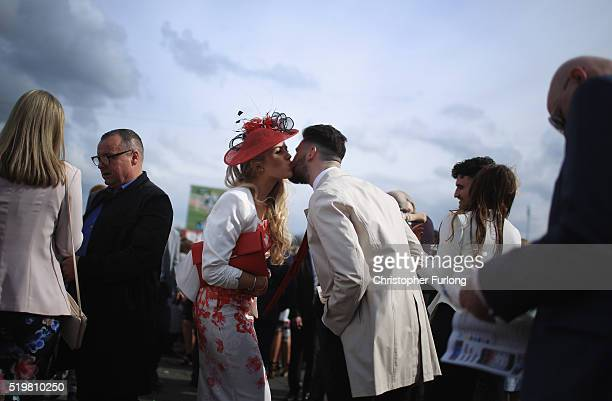 Two racegoers kiss as they enjoy the atmosphere of Ladies Day the second day of the Aintree Grand National Festival meeting on April 8 2016 in...