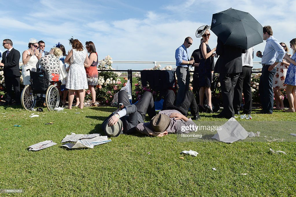 Two racegoers lie on the grass after the final race during Melbourne Cup Day at Flemington Racecourse in Melbourne, Australia, on Tuesday, Nov. 5, 2013. The Melbourne Cup, marketed as the race that stops the nation, is Australias premier thoroughbred horse racing event. Photographer: Carla Gottgens/Bloomberg via Getty Images