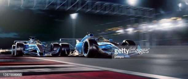 twee het rennen auto's die zich bij hoge snelheid tijdens de race van de nacht bewegen - autosport stockfoto's en -beelden
