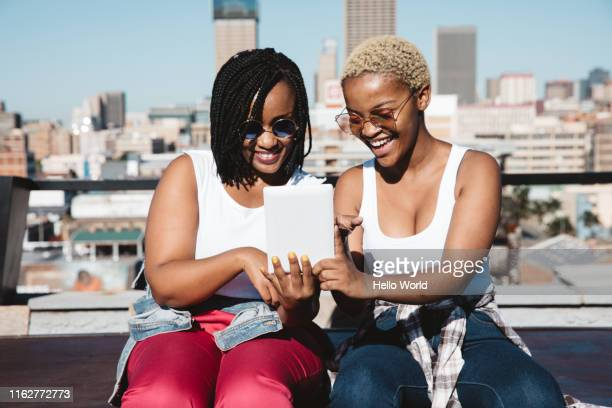 two radiant young women laughing whilst looking at digital tablet - curvy african women stock pictures, royalty-free photos & images