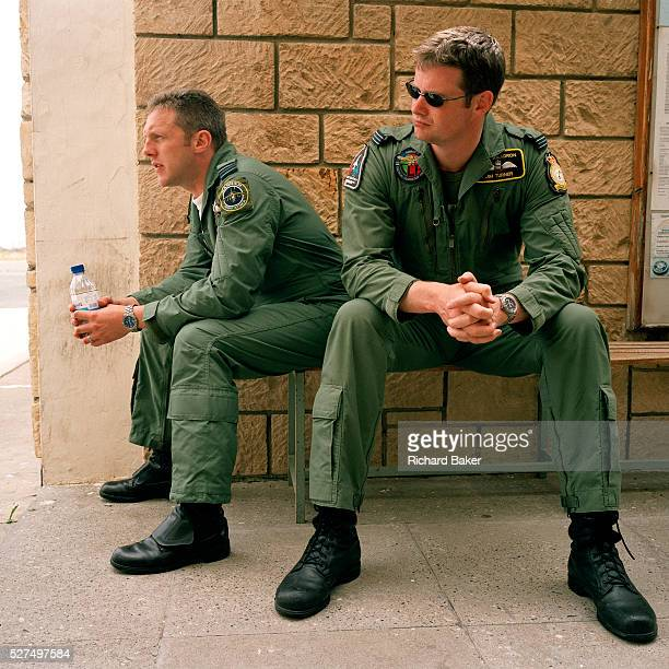 Two RAF fighter pilots listen to a preflightbriefing by the leader of the 'Red Arrows' Britain's Royal Air Force aerobatic team whose elite ranks...