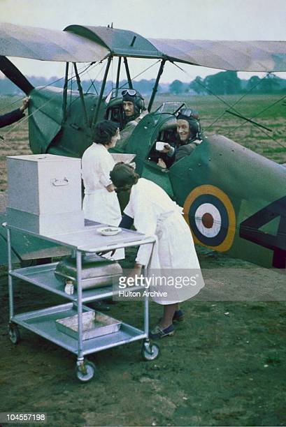Two RAF pilots are served tea by two tea ladies whilst sitting in their de Havilland Tiger Moth trainer circa 1940