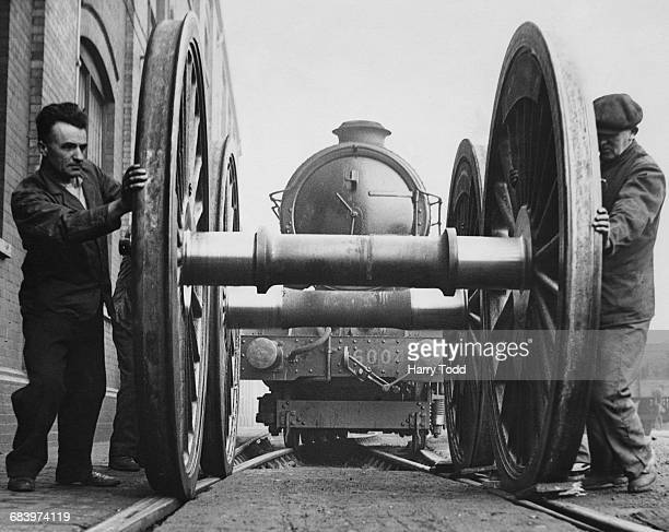 Two rail workers moving the driving wheels for the Great Western Railway 6000 Class or King class of 460 steam locomotives as the King George III...