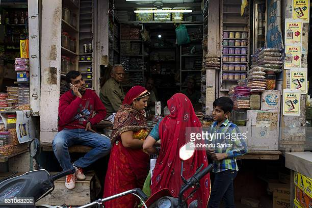 Two Rajasthani women in traditional dress in front of a shop