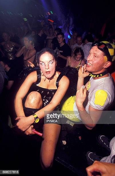Two ravers with novelty contact lenses and fluorescent clothes dance Cream Liverpool 2000s