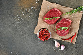 two raw beef steaks paper rosemary
