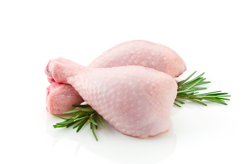 Two raw chicken legs on white backdrop 93456462