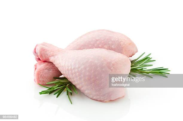 Two raw chicken legs on white backdrop