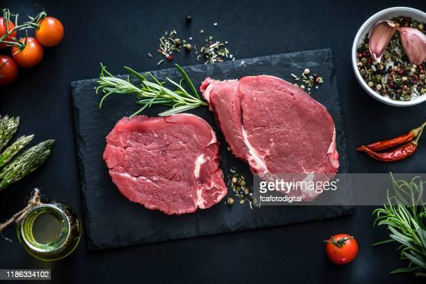 deux steaks crus de filet tiré d'en haut sur la table foncée - aliment cru photos et images de collection