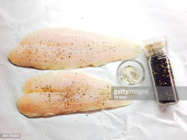two raw fillets of sole on white fish market paper seasoned with sea salt and fresh ground peppercorns in a grinder - linguado da areia imagens e fotografias de stock