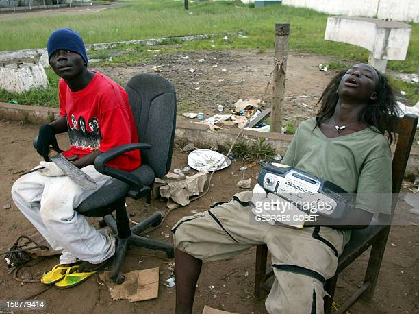 Two rebel soldiers of the LURD the rebels group of the Liberians United for Reconciliation and Democracy are seated at a checkpoint at one entrance...