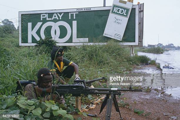 Two rebels from the National Patriotic Front of Liberia crouch in the brush underneath a cigarette advertisement telling them to Play it KOOL...