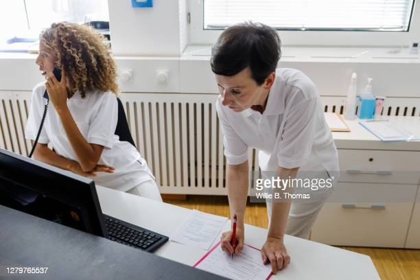 two receptionist busy working at front desk of mri clinic - medical receptionist uniforms stock pictures, royalty-free photos & images