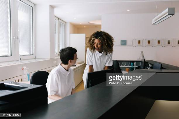 two receptionists talking while working in clinic - medical receptionist uniforms stock pictures, royalty-free photos & images
