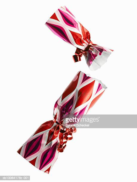 two red and pink party cracker on white background - クリスマスクラッカー ストックフォトと画像
