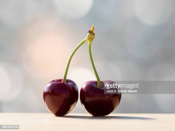 two red cherries on a table of wood illuminated by the light of the sun - due oggetti foto e immagini stock