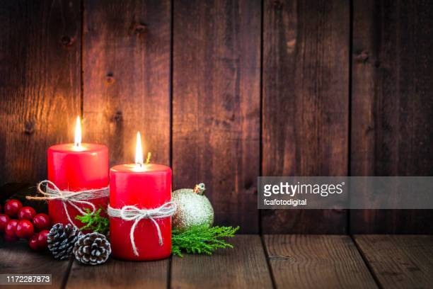 two red christmas candles on rustic table with copy space. - religion stock pictures, royalty-free photos & images