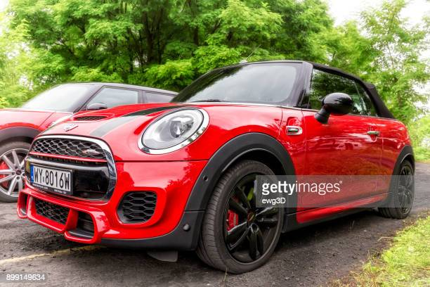 two red convertible 2 door  mini john cooper works at the road in the park - mini cooper stock photos and pictures