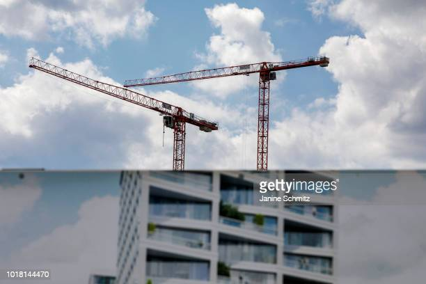 BERLIN GERMANY AUGUST Two red cranes for house construction are pictured behind an information wall on August 10 2018 in Berlin Germany
