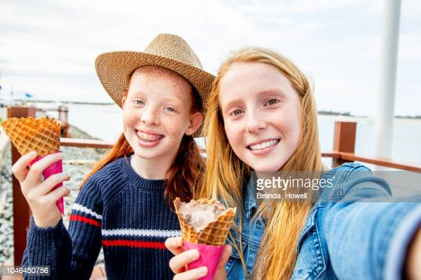 two red headed girls and little boy eat ice cream together by the ocean - self portrait photography stock pictures, royalty-free photos & images