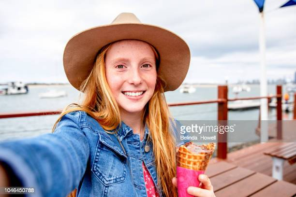 two red headed girls and little boy eat ice cream together by the ocean - selfie stock-fotos und bilder
