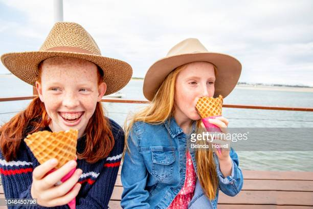 Two red headed girls and little boy eat ice cream together by the ocean