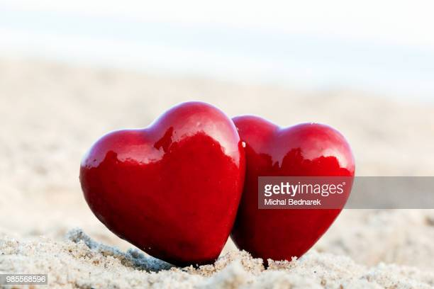 two red hearts on the beach symbolizing love, valentine's day, r - animal internal organ stock photos and pictures